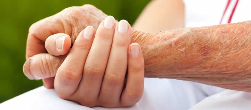 An older hand clasping a younger hand
